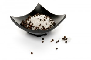 Whole Black Peppercorns and Crystal Sea Salt on Black Plate isolated on white background